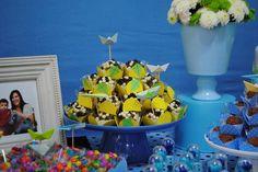 As forminhas de docinhos foram todas decoradas com pipas e os toppers dos docinhos foram origamis de barquinhos e aviões nessa festa de menino de um ano com o tema brinquedos de menino nas cores azul, verde e amarelo.