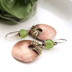 Wire wrapped dangle earrings with mixed metals. Leaf like quality earrings with green plastic, light weight, beads for a nice calm presents. I had