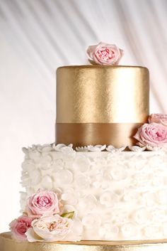 White and gold two tiered cake with flowers