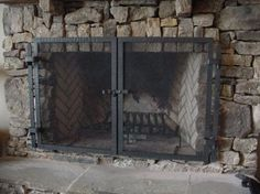 Unembellished fireplace screen with textured steel frame in front of rustic fireplace mantel with mesh fire screen.