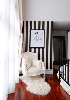 Sweet Home Style | feminine black and white reading nook with bold striped wallpaper, a fluffy faux fur rug and hardwood floors
