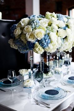 Tall centerpieces with white roses, blue hydrangea and white hydrangea.