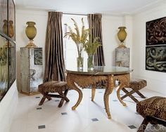 A 19th-century grotto-style table, Elsie de Wolfe stools, curtains of the Silk Trading Co.'s Como silk, and limestone floor tile by Exquisite Surfaces in the entrance hall of a flat in England; the photo series is by Guido Mocafico.