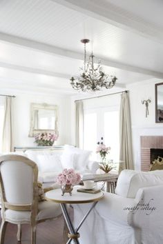 A palette of soft pastels and white slipcovered sofas create a dreamy living room. RELATED: Tour This French Style Cottage   - CountryLiving.com