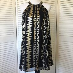 """One Clothing black & platinum party dress The perfect holiday party dress! So fun, so flirty. Floaty black poly chiffon with platinum """"tribal"""" design. Open shoulders, high neck that closes with two little gold tone buttons in back. Fully lined. NWT; never worn. One Clothing Dresses"""