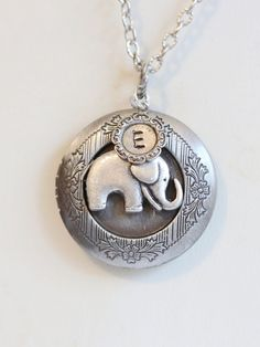 This is an interesting inspired silver baby elephant locket. A personalized hand stamped initial disc comes with this locket. Please leave me your letter of choice in the memo to seller box at check out. This locket measures 32mm and opens from the side. Two pictures can be places on the inside of the locket. Measurements: Locket on an 18 inch silver plated chain with a lobster clasp. ----------------------------------------------- All of items made by myself :