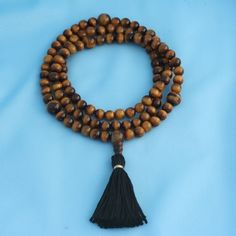 This 108-bead tigereye mala has large tigereye marker beads at the 7th place and 21st spots. Its strung with love and prayer on nylon-coated beading wire and finished it with a traditional three-holed tigereye guru bead and a black cotton tassel. Tigereye is a stone representing vitality, mental clarity, and strength. Symbolically, it represents overcoming fatigue and discouragement.  This mala can be worn gently as a necklace or around the wrist or used for your mantra and meditation…