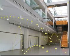 2,000 tennis balls suspended in Mustang Art Gallery in Alicante, Spain by Ana Soler-Causa-Efecto