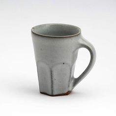Whita ash glaze reduction fired mug, since taking these to the first show I have now been making these a little larger and springing the handle of the mug a little more. By throwing them a little thicker in the base to allow me to facet the base it helps give them a really nice valence in the overall weight of the finished piece. Photograph by @floriangadsby #handmade #craft #ceramics #pottery #mug