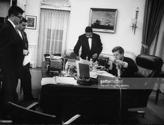 Pres. John F. Kennedy in his office with others.