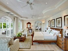 Plantation House bedroom, wood, beige, white and blue. Large room with french doors. Spotlights in the ceiling.