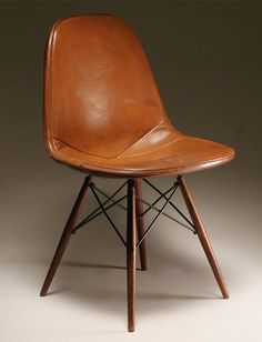 Vintage Eames with dowel legs and leather cover. Really nice in leather, and probably much better to use than the modern versions