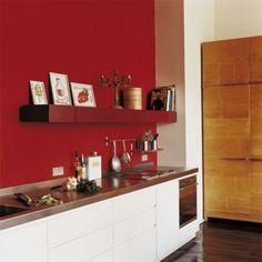 Une cuisine le long d'un comptoir face à un mur rouge