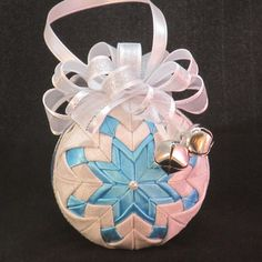 Item #: C238 Quilted Christmas Ornament - no sew fabric holiday ornament. Ornament is crafted with 100% cotton white with silver sparkle fabric, accented with turquoise satin fabric to create this uniquely designed ornament. Around the center of the ornament is a 3/8 turquoise sparkle ribbon. The decorative bow is made of 5/8 sheer silver ribbon and 3/8 silver sparkle ribbon. The ornament is embellished with two silver jingle bells. Measurements of completed ornaments: • Appr...