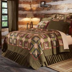 Tea Cabin quilt and bedding collection by VHC Brands distinguished by intricately detailed piecework and hand quilting. Eight point stars connect classic log cabin patches in this authentic tea stain quilt. Quilt is stitched in cotton plaid fabrics of navy, burgundy, cream, green and tan and framed in a mossy green border. Due to the tea stain process, each piece is uniquely colored, making this an heirloom-quality quilt.