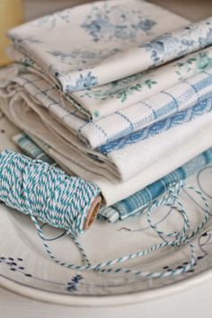 Stack of Blue & White Linens in Various Designs, and a Spool of Blue & White Baker's Twine