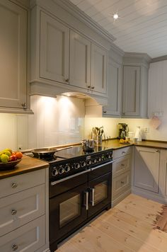 Hand painted light gray kitchen in solid pine from Os Trekultur. Worktop in stained and varnished oak. 110 cm wide Falcon oven with 5 cooking zones, double ovens and grill.