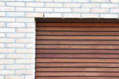 Een lichte steen gecombineerd met meranti houten latten op de garage deur