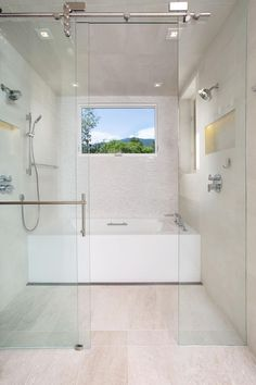 This contemporary bathroom incorporates a wet room area with a no-threshold shower and a separate soaking tub. A large window allows natural light to illuminate the space.