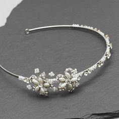 A feminine freshwater pearl and crystal side tiara.This piece features sparkling Austrian crystals, freshwater pearls and small glass beads to create two beautiful flower details. The bead detailing really adds to the nostalgic effect and is a really pretty feature for a vintage wedding. This is a fantastic piece for bridesmaids. This item comes in a modern ivory-coloured presentation box.The tiara is crafted using the world's best quality Austrian crystals by Swarovski, freshwater pearls…