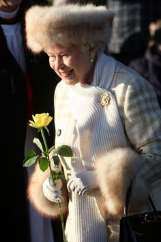 The Hats of Queen Elizabeth's Monarchy:  With her fox-fur headband, a tweed coat, and a softly lopped scarf held in place with a brooch, the Queen's cushier, more pastel elder style is a sharp contrast to her primary-color turbans of the 1970s. Here, she clutches a yellow rose while celebrating Christmas at Sandringham, her other country estate, in 2010.