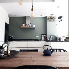 Deze stijlvolle witte keuken met greeploze deurtjes krijgt een warme uitstraling door de groene muur (de kleur PALAU van de GAMMA) en de houten eettafel.