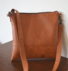 This cross-body / shoulder bag is handmade of distressed tan, vegan leather.  Perfect everyday bag.  Closes with a zipper. The interior is fully lined.  Measurements: 11 x 11  - adjustable and removable strap - two inside pockets - flat construction - simple and trendy design - handmade  Visit my shop for more items: http://www.etsy.com/shop/reabags  Thanks for looking