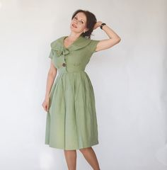 The most adorable 50s dress ever! Sailor collar that ends in a bow in the front. Big asymmetrical, textured wooden buttons   on the bodice. Metal side zipper. Hourglass waist. Flared, pleated, knee length skirt that is lined with an underskirt that feels kind of like paper. The green fabric feels like a woven cotton. possibly blended. The fabric surface is textured with squares. There´s minor piling, but I think that it´s just because it´s woven to look that way.     Label: -    Size: Small…