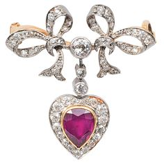 A diamond brooch with a ruby pendant. 18 ct. white gold with yellow gold. Brooch with ornaments of bows and all together 60 diam. in old and rose cut (36 old cut diam. in total c. 0,60 ct. H-J.vsi-P) and 1 ruby in pear cut c. 1,40 ct. (8 x 6 mm). 32 x 30 mm, weight c. 8 g.