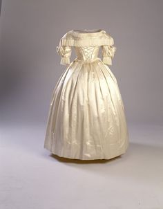 Historic New England C. 1839- 40 Cream silk satin wedding dress; bateau neck trimmed with cream fringe; attached capelet extends over shoulders with twisted silk satin braid and same silk fringe; bodice has satin lattice amd twisted satin braid to waist; silk fringe at slightly pointed waist; piping at armseye; pleats at drop shoulder broken by teo rows of satin rope braid; elbow length; two rosettes at elbow with same silk fringe. Five silk satin rosettes at center back; hook and eye closure. …