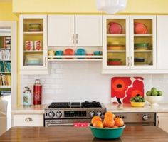 Trendy kitchen with pops of color, open cabinets and fun dishes. Yellow kitchen walls and white cabinets. Red dishes, teal dishes, green dishes. image MP Builders Finish Carpentry, Millwork Installation, Home Remodeling Cincinnati Ohio
