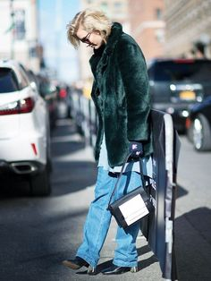 An emerald green fur coat is worn with wide leg jeans, a two-tone bag, and black booties