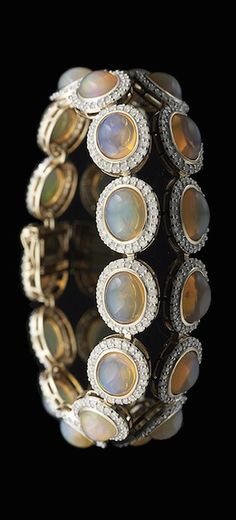 Fourteen-Karat Yellow Gold, Opal and Diamond Bracelet, composed of thirteen oval-shaped cabochons, with an approximate total weight of 15.26 carats, each surrounded by a halo of round brilliant-cut diamonds, with an approximate total weight of 2.79 carats. #opalsaustralia