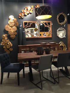 Dramatic denim grey wall appointed with gold sculptures and a collage of mirrors to add sparkle.