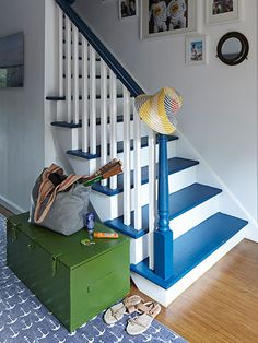 A Garnet Hill rug and porthole-shaped mirror reinforce the nautical vibe of this family-friendly New York home's staircase, painted in Benjamin Moore's Big Country Blue. The trunk was a flea-market bargain. Painted Stair Risers, Painted Staircases, Stairs Balusters, Bannister, Farmhouse Stairs, Escalier Design, White Stairs, New York Homes, Staircase Design