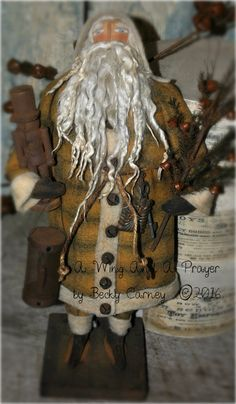 Olde World Santa is mounted on a primitive wood base and he measures 17 tall. He has hand painted blue eyes, a stitched sculpted nose and blushed cheeks. his beard, brows and hair are made of raw Suri Alpaca Locks. He has wired arms and painted on gloves and boots. He is dressed in a Mustard Brown Plaid Felted wool coat, all trimmed with needle felted wool roving, rusty bells and a rope belt. A old rusty chocolate mold and old key hangs on one side. In one hand he holds a Primitive tree…