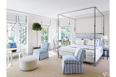 A guest room is outfitted with a four-poster designed by Bruce Budd, floor lamps by Vaughan, and a raffia-and-cotton carpet from Beauvais; a Rose Cumming stripe dresses the headboard and slipper chairs, the fringed throw is by Loro Piana, and the walls and ceiling are sheathed in an Elizabeth Dow linen.