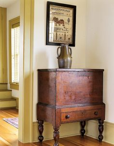 """As a college student, Duggin received visits between classes from """"pickers,"""" local dealers who knew his tastes. """"I kept careful records of what I bought and had to sell for tuition, so I was able to buy back those pieces."""" A circa 1820 sugar chest looks gorgeous against mustard-colored walls and decorated with antique pottery.   - CountryLiving.com"""