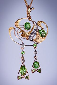 A Russian Art Nouveau Demantoid and Diamond Pendant Necklace, made in Kazan 1908 - 1917. The openwork pendant of a floral design set with Russian demantoid garnets and diamonds in 14K greenish yellow gold and silver.