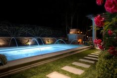 Deck jets, or water arches, spout into this raised swimming pool for fun water feature. Plush grass surrounds the pool, taking the place of traditional concrete pool decks.