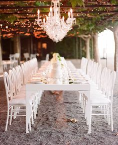 glamour and pretty rustic wedding table setting under a vine filled pergola for a barn wedding