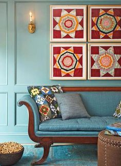 Home renovation:  Family Room :  Framed antique quilt fragments hang above the Federal-style settee upholstered in Mermaid blue.  Posted at Traditional Home