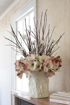 Amaryllis stems with tall red branches in the center mixed with a few cut paperwhites are arranged in a white bark container.  Design by Karin Lidbeck Brent, Photography by Michael Partenio
