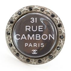 This is an authentic CHANEL Crystal 31 Rue Cambon Paris Coco Mania Brooch.   This stunning disk brooch is crafted of different metals a large darker metal central disk with the engraved Chanel flagship store location address and a surrounding border of light metal with evenly spaced stars that alternate with cut dark metal faux gems with miniature studs in between.