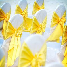 Yellow bows on white chair covers.