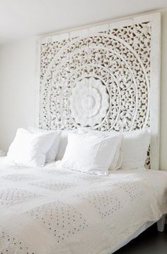 Rooms tend to have some sort of focal point. This is in order to let the room be balanced. Above is a carved headboard in a white contemporary room