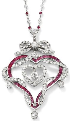 A ruby diamond heart pendant necklace. Designed as a calibre-cut ruby openwork heart entwined by a line of brilliant-cut diamonds suspending a central similarly cut diamond heart, to a diamond bow surmount, millegrain-set diamond drop highlights, and suspended on a spectacle-set ruby and diamond chain, length 41 cm, pendant length 6.2 cm. Via Phillips.