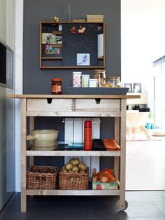 A kitchen trolley with wicker baskets on shelves, tray on top and wall shelving above