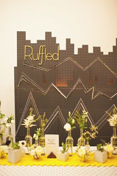 pegboard backdrop. Used two pieces of pegboard that were cut into a cityscape and painted charcoal. Rope lights were used behind it to create the glow. The Ruffled logo was made out of foam board and wrapped tinsel.