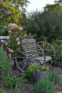 Wagon Wheel Bench Surrounded by Flowers